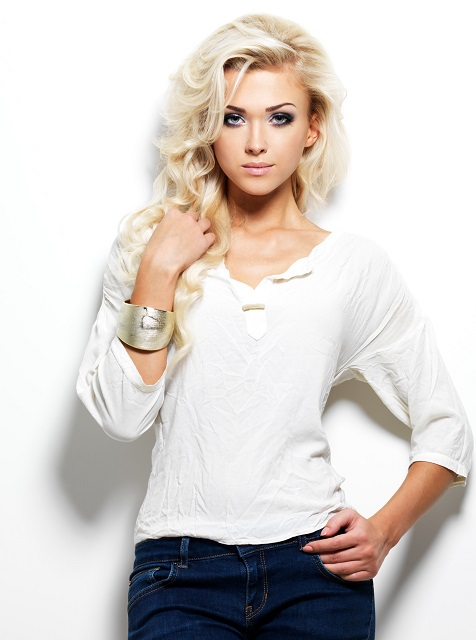 Fashion model posing in studio. Portrait of a beautiful blond woman with saturated makeup. Girl posing on white background