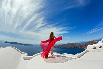 Woman in red dress aerial on the roof of island Santorini